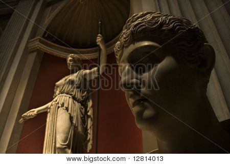 Close-up of head of sculpture with figure sculpture in background in the Vatican Museum, Rome, Italy.