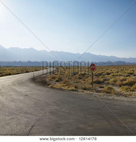 Carretera con señal de stop en el árido paisaje con la montaña en la distancia.