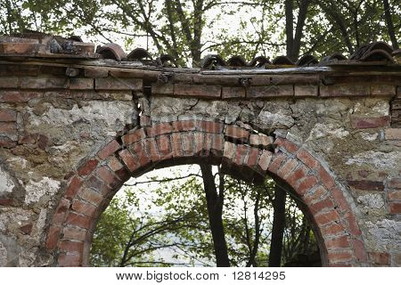 Dilapidated stone archway with trees in background in Tuscany, Italy.