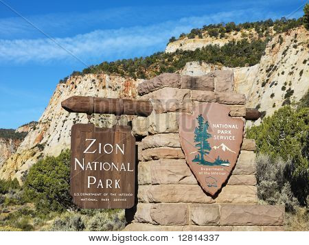 Wooden and stone sign for Zion National Park, Utah with rocky cliffs in the background.