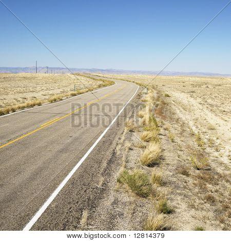 Road through barren landscape in Utah.