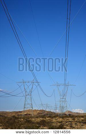 Electrical power lines in barren desert landscape.