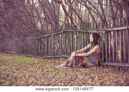 Hippie girl leaned against the vintage fence
