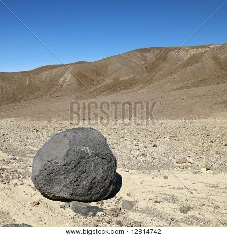 Boulder in barren landscape in Death Valley National Park.
