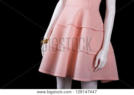 Short salmon dress with bracelets. Evening dress on black background. Girl's precious accessories and clothing. Clothes for night out.