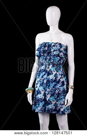 Sleeveless blue summer dress. Mannequin wearing floral pattern dress. Girl's dress on dark background. Light vintage dress on sale.