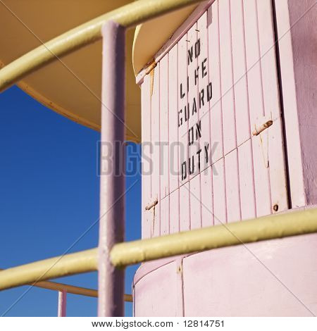 Close-up of pink art deco lifeguard tower with no lifeguard on duty sign in Miami, Florida, USA.