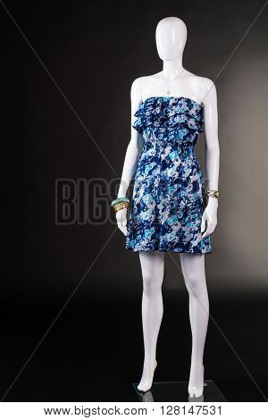 Short blue dress without straps. Strapless floral dress on mannequin. Summer clothing on black background. Woman's vintage style garment.