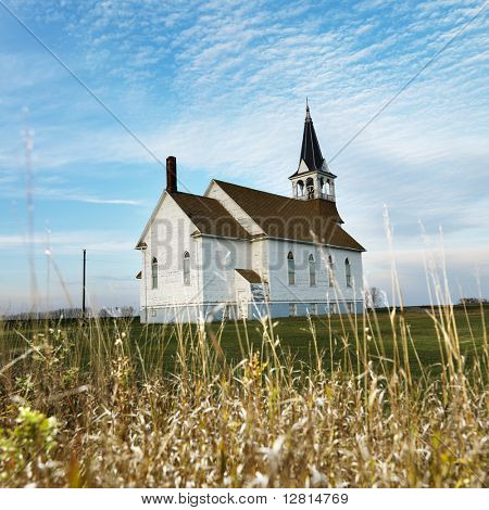 Small rural church in field with chipped wood siding.