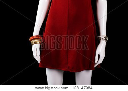Bracelet, watch and red dress. Set of bracelets on mannequin. Woman's stylish watch and bijouterie. Special offer in boutique.