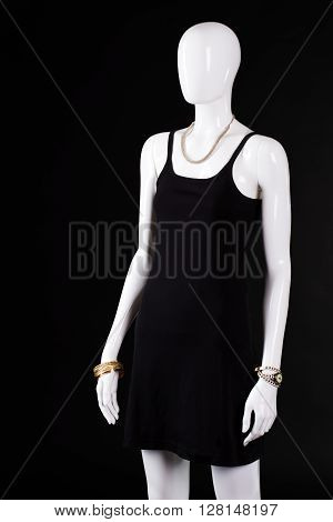 Black casual dress with accessories. Mannequin wearing simple dark dress. Woman's casual evening look. Gold bracelet and dark garment.