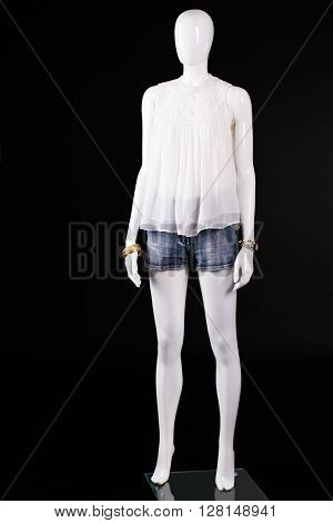 White top and denim shorts. Female mannequin in white top. Summer outfit on dark background. Young lady's stylish look.