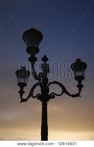 Streetlamp with sunset sky in background in Rome, Italy.