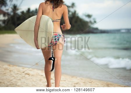 Shot of the young lady walking with surf board on sandy tropical beach