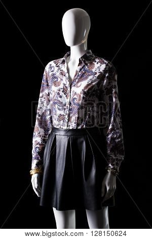 Dark floral shirt and skirt. Female mannequin wearing dark clothes. Stylish mannequin on black background. Woman's classy evening apparel.