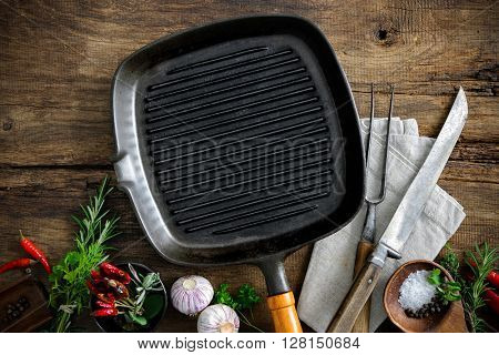 Empty grill pan with seasonings and meat fork on wooden background