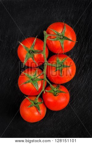 Bunch of fresh red tomatoes on a black slate background. Top view