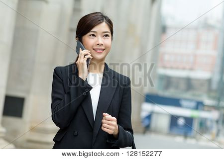Business woman walking and calling by cell phone