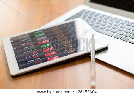 Digital stock market chart on white tablet screen