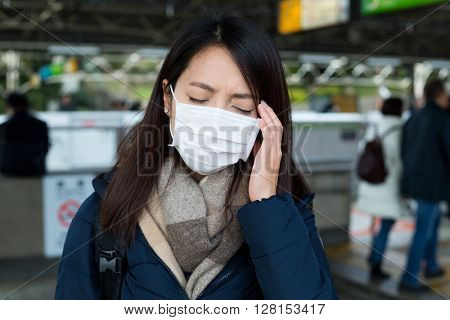 Woman with face mask and feeling headache