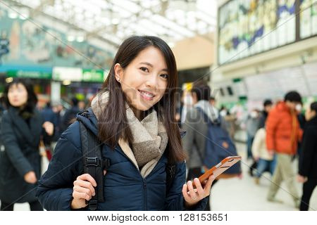 Woman use of cellphone in train station
