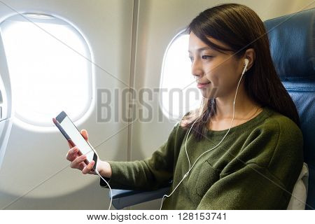 Woman listen to music on cellphone at the plane