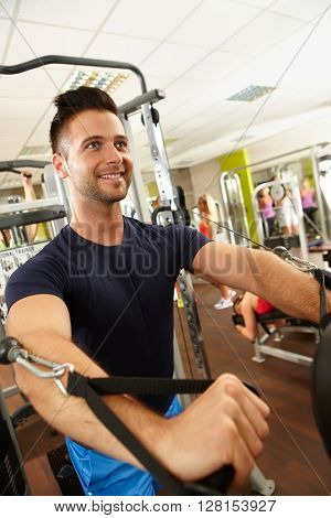 Happy young man training in gym on weight machine.