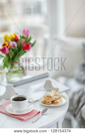 White cup of the coffee and sweets on wooden table  in a light room..