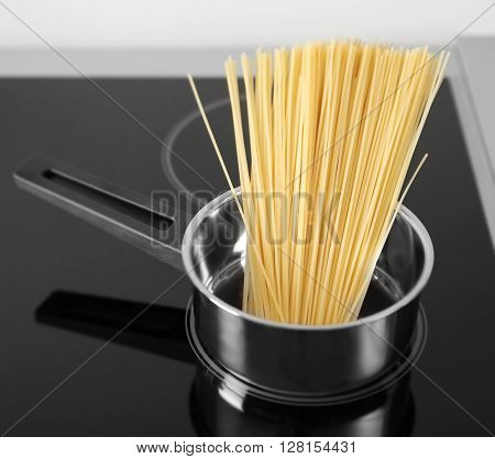 Boiling spaghetti in pan on electric stove in the kitchen