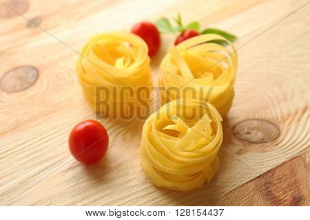 Nests of dry noodles on wooden table