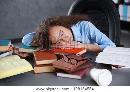 Tired beautiful girl sleeping on table