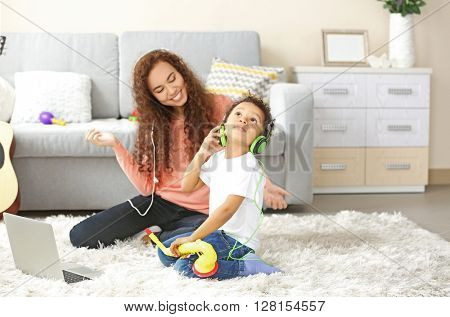 Young woman in headphones listens little boy playing on toy saxophone.