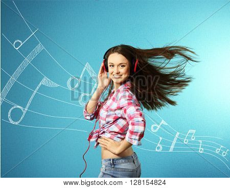 Young woman listening to music and dancing against blue background