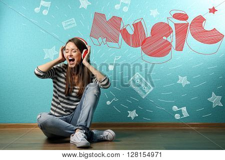 Young woman sitting on floor and listening to music against blue wall