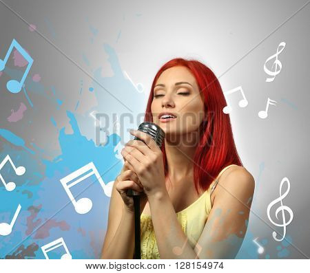 Beautiful woman singing into microphone against grey background