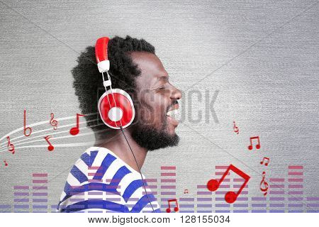 African American man with headphones listening to music against grey background