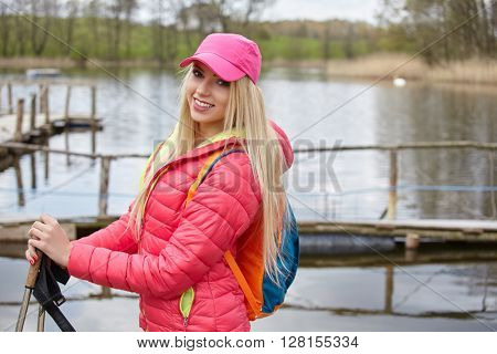 Joyful blond girl dressed in sport with poles Nordic walking on the lakeside holidays.