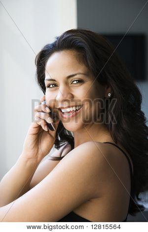 Hispana adulta joven mirando al espectador y hablando por teléfono celular.