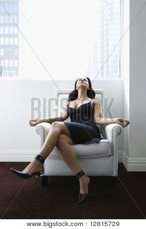 Hispanic woman relaxing in armchair with window to city in background.