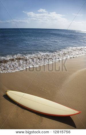 Surfboard on sandy beach with ocean in background in Maui Hawaii.