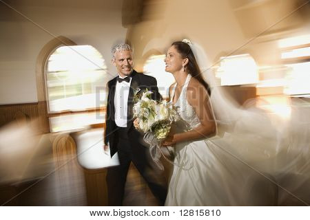 Bride and groom leaving church with motion blur effect.