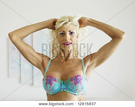 Tan Caucasion blonde middle-aged woman posing in bra with arms over head.