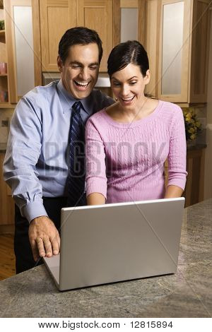 Mid-adult couple in kitchen looking and smiling at laptop computer.