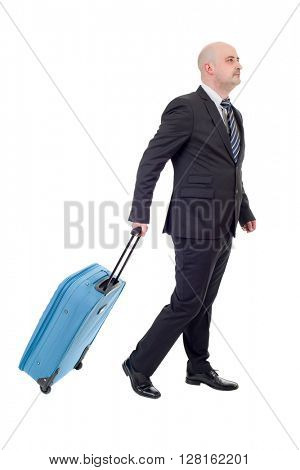 Full length side view of young businessman with luggage walking isolated on white background