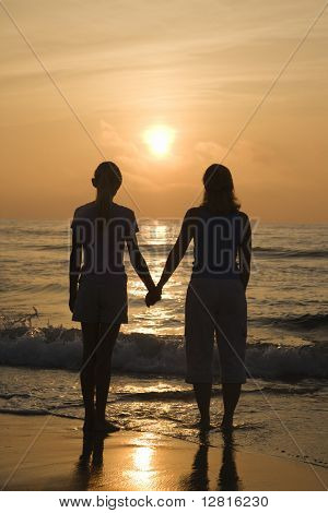 Caucasian mid- female and teenage daughter standing on beach at sunset holding hands.