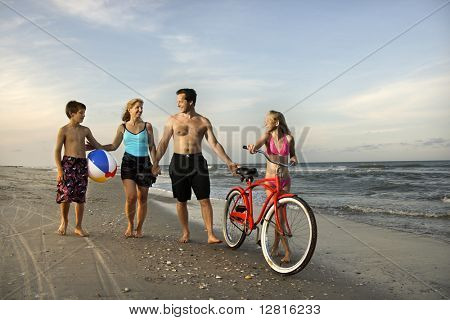 Caucasian family of four walking on beach.