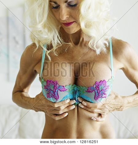 Tan Caucasion blonde middle-aged woman in bra, squeezing breasts to enhance cleavage.