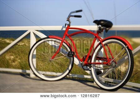 Red beach cruiser bicycle leaning against walkway rail on beach on Bald Head Island, North Carolina.