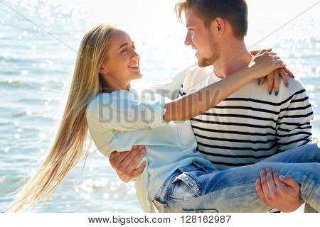 Young man holding on the hands his a cute girlfriend