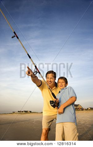Caucasian mid-adult man shore fishing on beach with pre-teen boy and pointing.